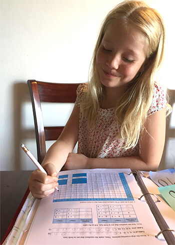 Girl filling in multiplication table from Math Mammoth page
