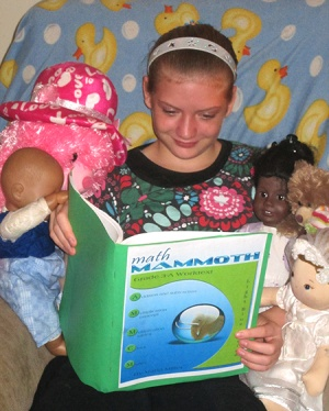 child studying Math Mammoth grade 3-A student book, with dolls